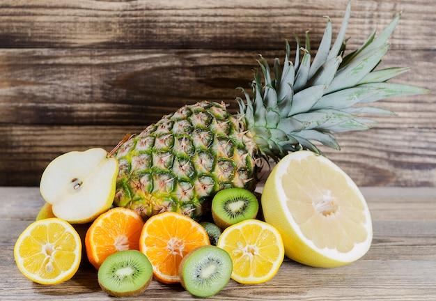 Ananas et tranches de citron, kiwi, pamela et poire empilés sur un fond de bois Photo Premium
