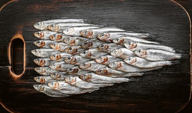 Anchois et sprat de poisson cru frais sur une surface en bois Photo Premium