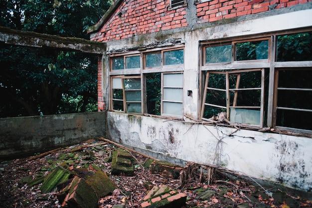 Ancien Bâtiment Abandonné Avec Des Fenêtres Détruites Dans La Forêt Photo gratuit