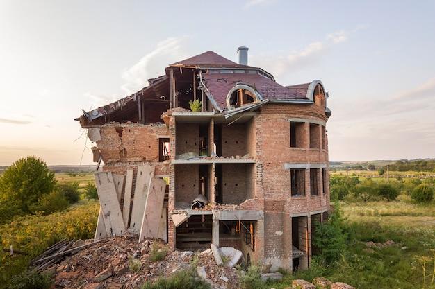 Ancien bâtiment en ruine après le tremblement de terre. une maison de briques effondrée. Photo Premium