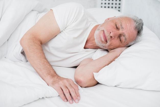 Ancien homme dormant dans un lit blanc Photo gratuit