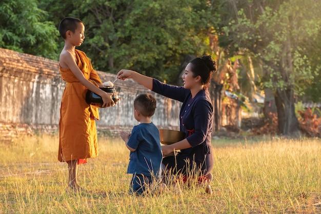 Ancien novice bouddhiste. la famille une femme qui met des offrandes dans un bol à aumône pour un moine et une femme qui se prosterne pour respecter les moines adorateurs, des moines marchant chaque matin. Photo Premium