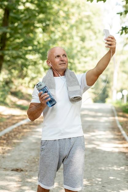 Ancien prenant selfie dans un vêtement de sport avec une serviette Photo gratuit