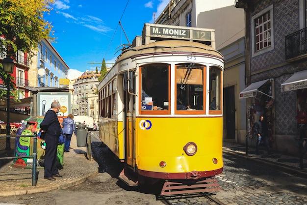 Un ancien tramway traditionnel dans le centre-ville de lisbonne, au portugal. la ville a gardé le vieux tram traditionnel en service dans la partie historique de la capitale Photo Premium