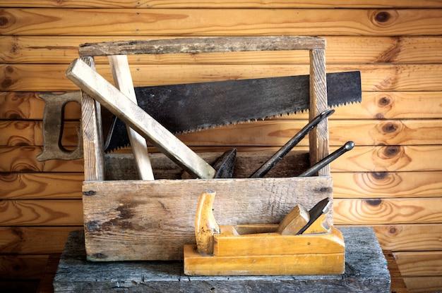 Ancienne boîte à outils vintage avec marteaux, scie, avion et pinces de menuiserie Photo Premium