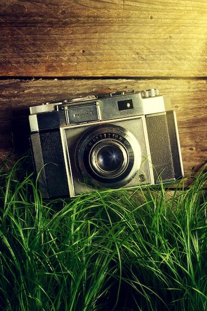 Ancienne Caméra Vintage En Herbe Verte Avec Des Rayons Lumineux Sur Fond En Bois. Vue De Dessus. Photo gratuit