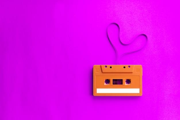 Ancienne cassette audio avec un coeur en forme de film sur fond rose. Photo Premium