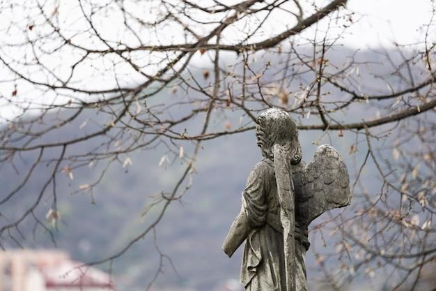 Ancienne Sculpture En Pierre Tombale D'un Ange Avec Bras Et Ailes Cassées Sur Le Cimetière Photo Premium