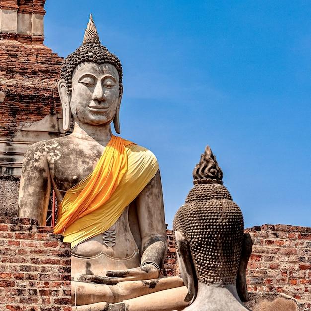 Ancienne Statue De Bouddha Recouverte De Tissu Jaune Photo gratuit