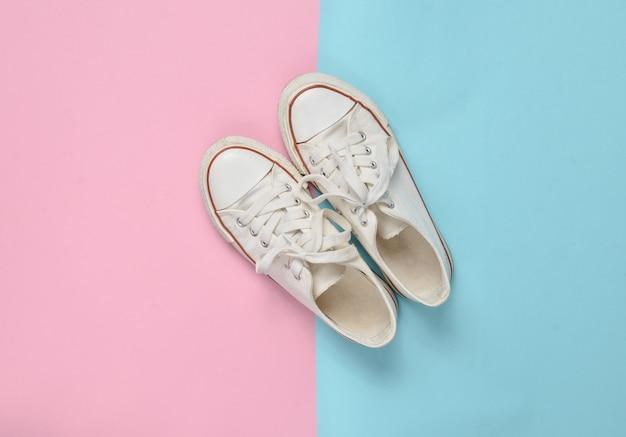 Anciennes Baskets Rétro à Lacets Blancs Sur Fond Pastel Rose Bleu. Le Minimalisme. Vue De Dessus Photo Premium