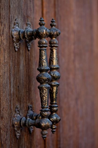 Anciennes poignées de porte en métal italien sur porte en bois marron. Photo Premium