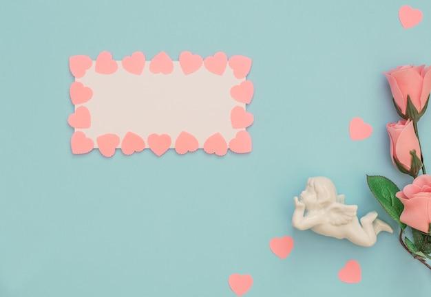 Ange Blanc, Feuille Vierge Avec Cadre Coeurs Roses Et Roses Sur Bleu Photo Premium