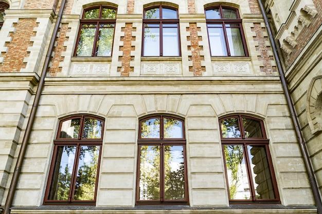 Angle Bas De Fenêtres Cintrées Sur Le Vieux Bâtiment Magnifique Avec Reflet Du Ciel Et Des Arbres Dans Le Verre Photo gratuit