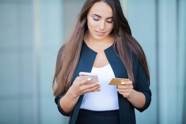 Angle bas de la fille heureuse debout dans le hall de l'aéroport. il utilise une carte de crédit et un téléphone portable gold pour payer Photo Premium