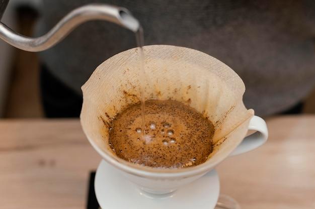 Angle élevé De Barista Masculin Verser De L'eau Chaude Sur Le Filtre à Café Photo gratuit