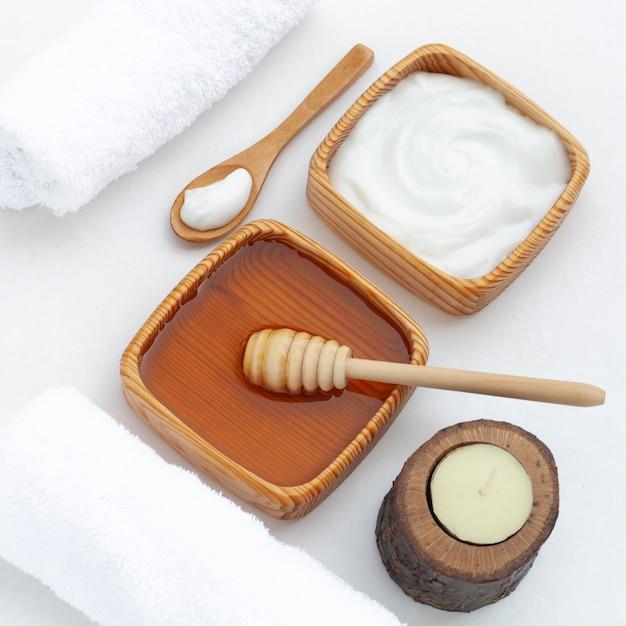 Angle élevé de beurre corporel et de miel sur fond blanc Photo gratuit