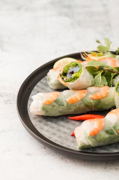 Angle élevé de crevettes roule sur une assiette avec une sauce Photo gratuit