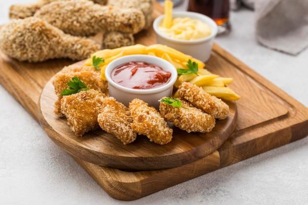 Angle élevé De Cuisses De Poulet Frit Et Pépites Avec Sauce Photo Premium