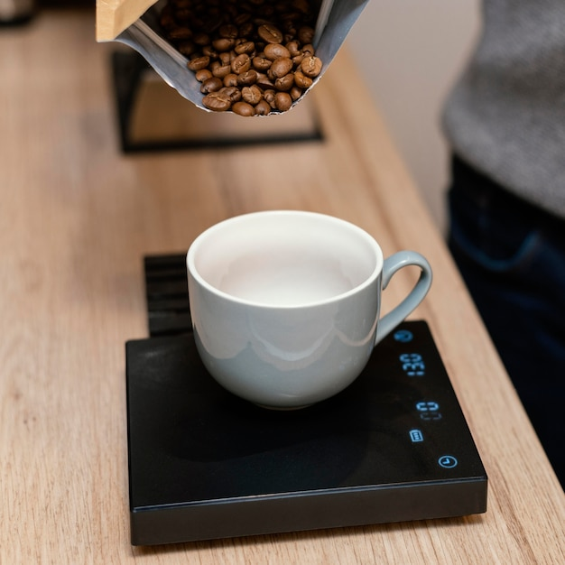 Angle élevé Du Barista Masculin Pesant Les Grains De Café à L'aide De L'échelle Photo Premium