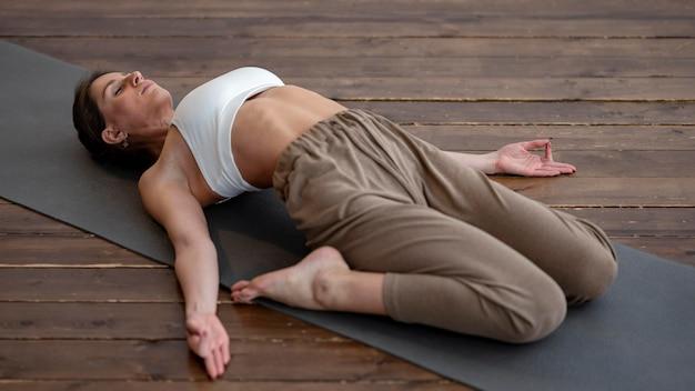 Angle élevé De Femme à La Maison Pratiquant Le Yoga Photo gratuit