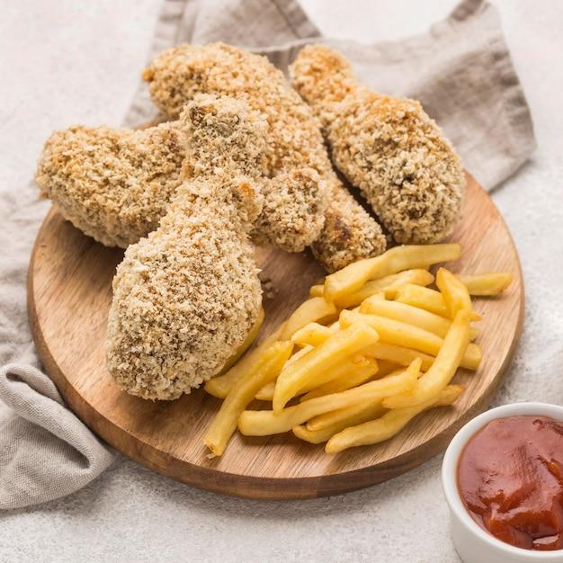 Angle élevé De Frites Avec Cuisses De Poulet Frit Et Sauce Photo gratuit