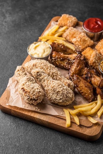 Angle élevé De Frites Avec Des Sauces Et Du Poulet Frit Photo gratuit