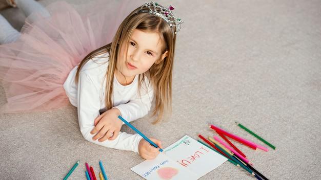 Angle élevé De Jolie Fille Tenant Une Carte à Dessin Pour La Fête Des Pères Photo gratuit