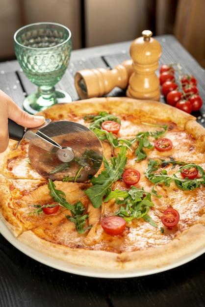 Angle élevé de main coupe pizza sur une table en bois Photo gratuit