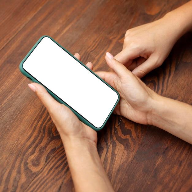 Angle élevé Des Mains De Femmes Tenant Le Smartphone Photo gratuit