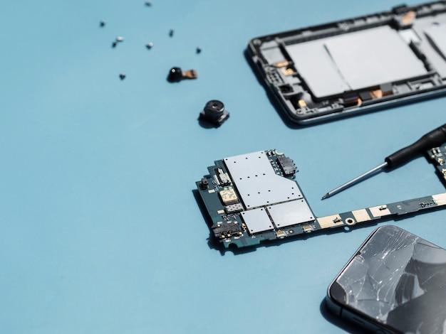 Angle élevé de pièces de téléphone sur fond bleu Photo gratuit