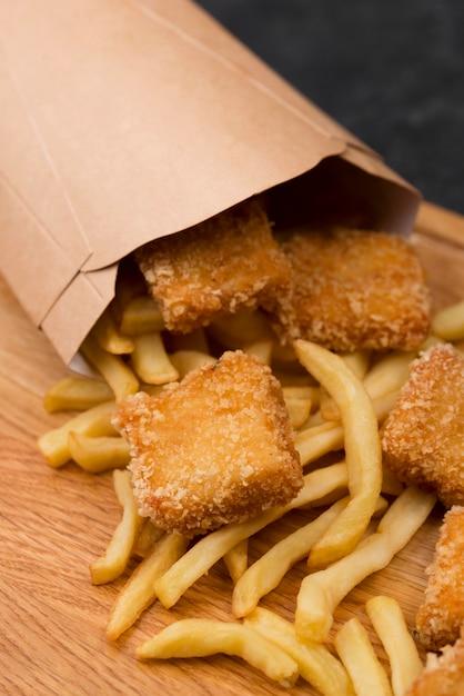 Angle élevé De Poulet Frit Avec Frites Et Sac En Papier Photo gratuit