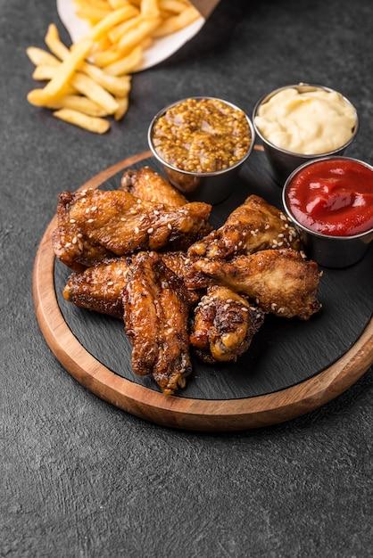 Angle élevé De Poulet Frit Avec Une Variété De Sauces Et De Frites Photo gratuit