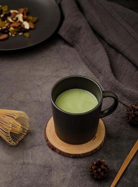 Angle élevé de tasse de thé matcha sur les montagnes russes Photo gratuit