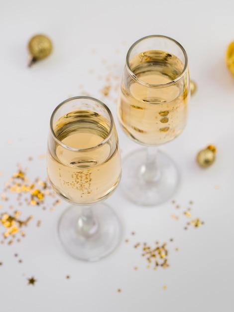 Angle élevé de verres à champagne avec des paillettes dorées Photo gratuit