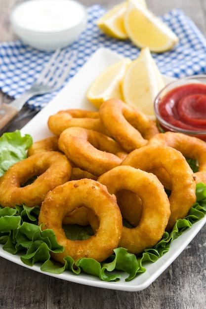 Anneaux De Calamars Frits Avec De La Laitue Et Du Ketchup Sur Une Surface En Bois Photo Premium