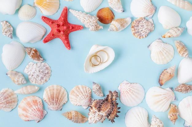 Anneaux sur une coquille sur un fond bleu de l'été avec différents coquillages et étoiles de mer Photo Premium
