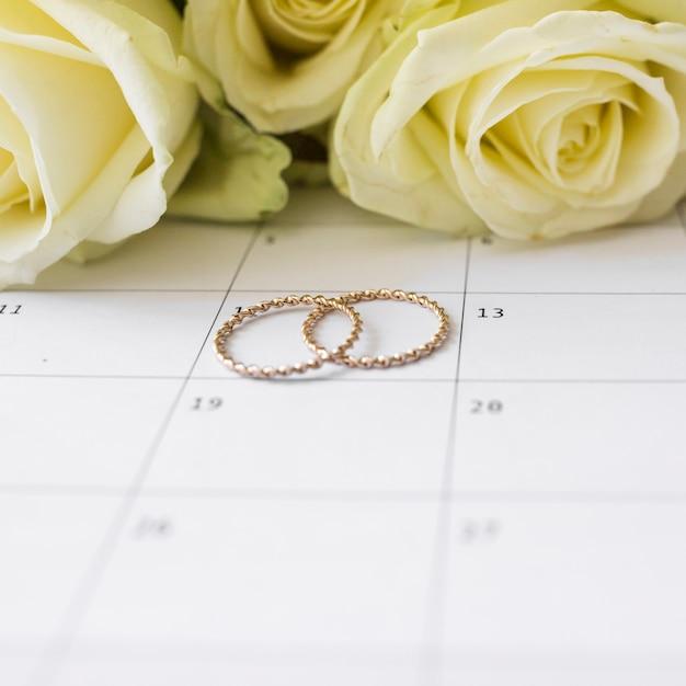 Anneaux de mariage à la date du calendrier avec des roses jaunes Photo gratuit