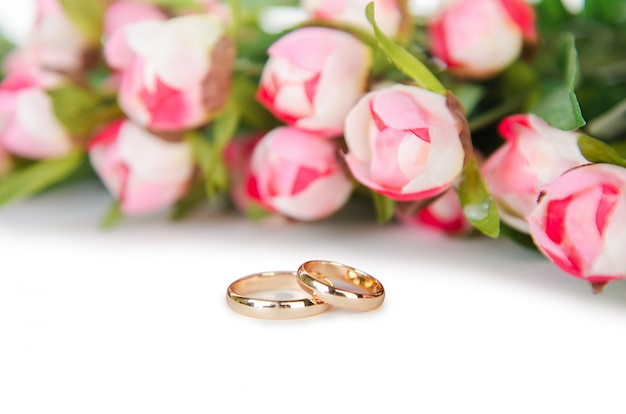 Anneaux de mariage et fleurs isolés sur fond blanc Photo Premium