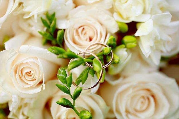 Anneaux de mariage gros plan sur le bouquet. décoration de mariage Photo Premium