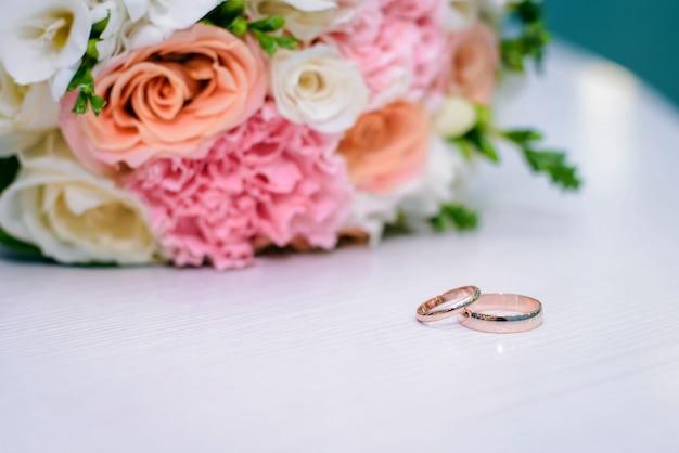 Anneaux De Mariage En Or Et Bouquet De Mariée Sur Une Surface Blanche Photo Premium