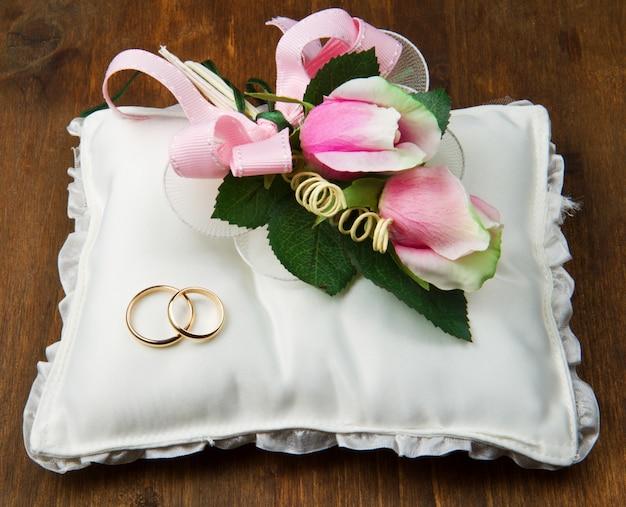 Anneaux de mariage avec des roses sur l'oreiller de mariée Photo Premium