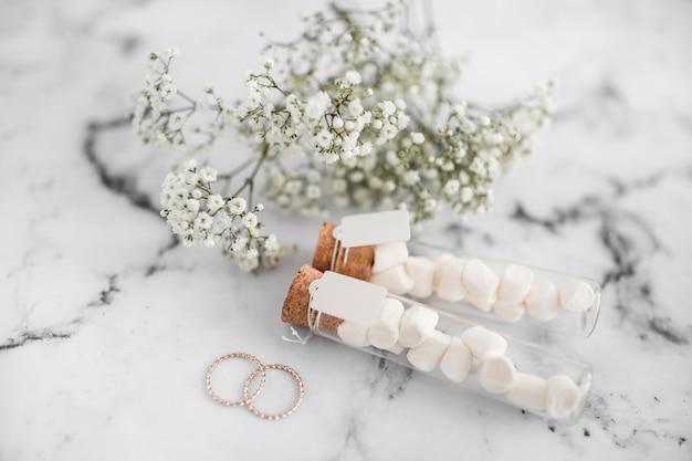 Anneaux de mariage; tubes à essai guimauve avec étiquette et fleurs d'haleine de bébé sur fond texturé blanc Photo gratuit