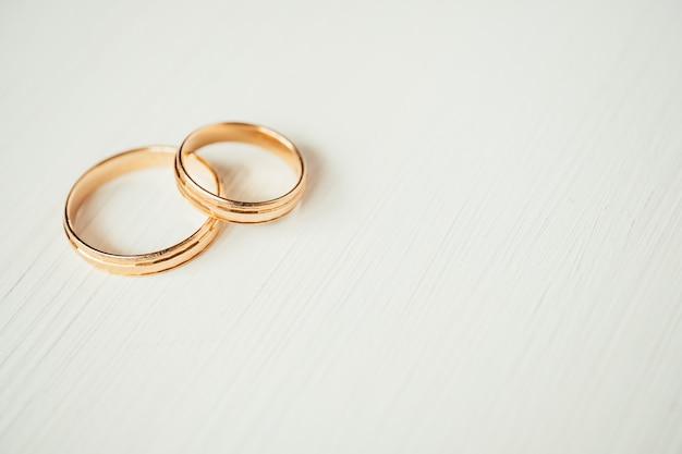 Anneaux d'or de mariage qui se croisent dans la partie gauche d'un fond en bois blanc Photo Premium