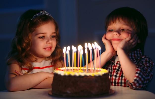 Anniversaire des enfants. enfants près d'un gâteau d'anniversaire avec des bougies. Photo Premium