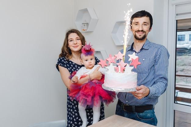 Anniversaire d'une petite fille. maman, papa et une jolie petite fille avec un gâteau Photo Premium