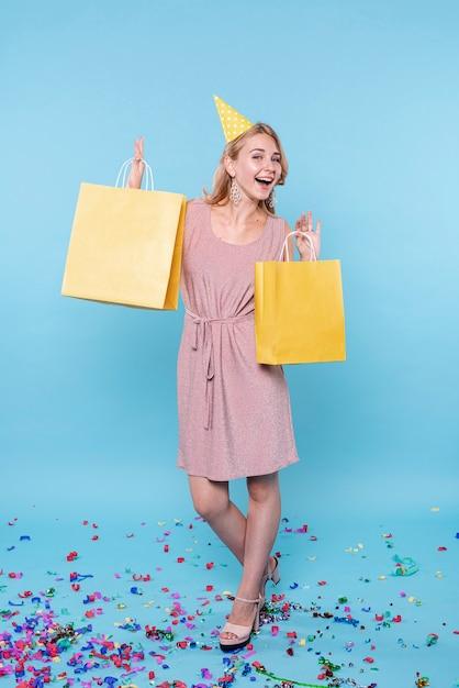 Anniversaire sortie femme tenant des sacs de cadeaux Photo gratuit