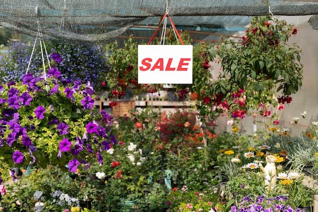 Annonce De Vente Sur Une Feuille De Papier Suspendue Au-dessus D'une Variété De Fleurs à L'intérieur De La Serre Ou D'une Boutique De Fleurs Photo Premium