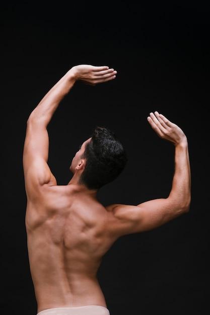 Anonyme mâle dansant avec les bras levés Photo gratuit