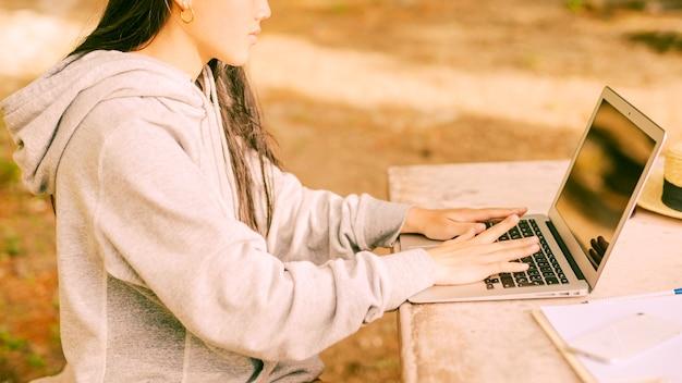 Anonyme en sweat à capuche confortable assis et tapant sur un ordinateur portable Photo gratuit