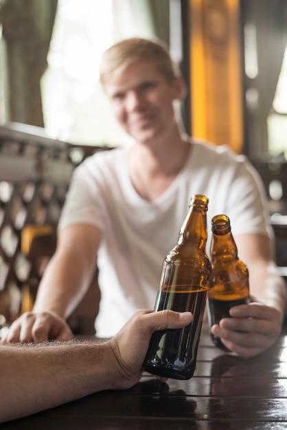 Anonymes hommes clinking bouteilles à la table de pub Photo gratuit